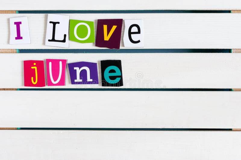 Amo junio escrito con recortes de la letra de la revista del color en el tablero de madera Concepto de las vacaciones de verano,  fotos de archivo libres de regalías