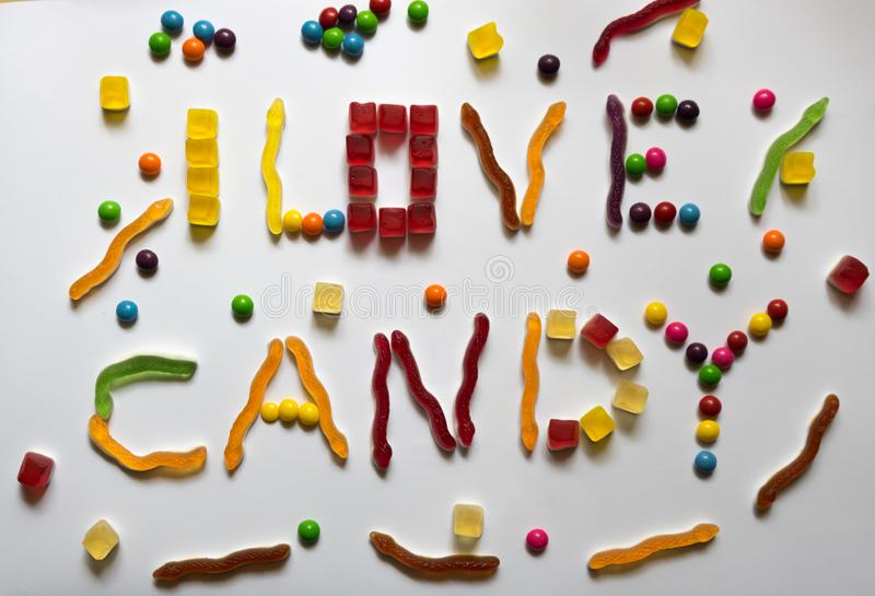 Amo la frase della caramella fatta dai dolci variopinti differenti su fondo bianco fotografia stock