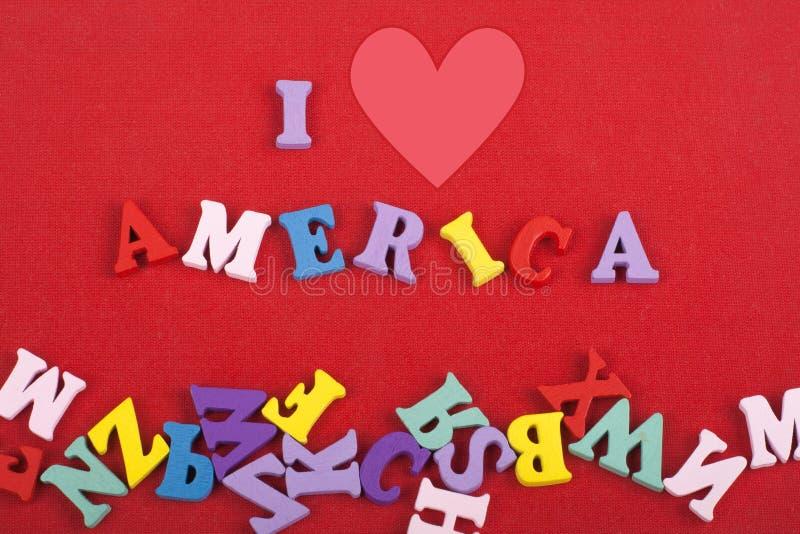 Amo la parola dell'America su fondo rosso composto dalle lettere di legno di ABC del blocchetto variopinto dell'alfabeto, copio l fotografia stock