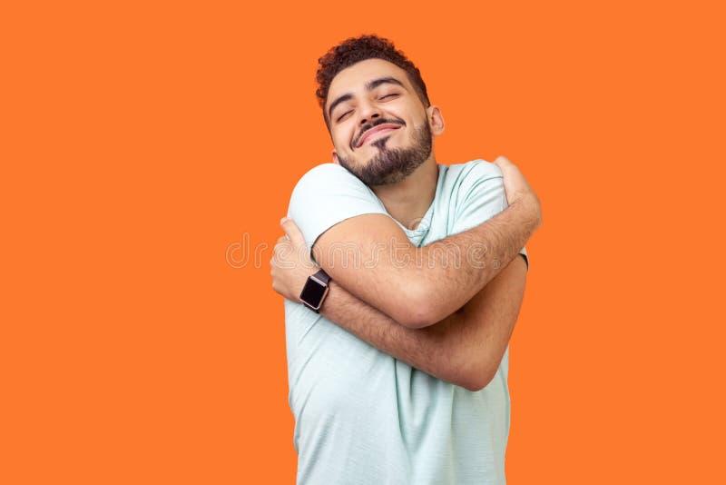 Amo me stesso! Ritratto di brunetta egoista che si abbraccia e sorride di gioia studio interno isolato in arancione immagini stock libere da diritti