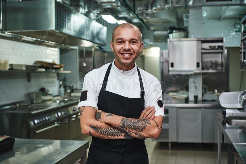 Amo a mi cocinero joven alegre del trabajo en el delantal que mantiene los brazos tatuados cruzados y que sonríe mientras que se  fotos de archivo libres de regalías