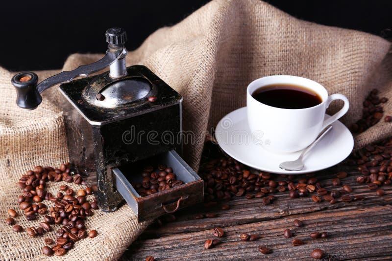 Amoladora de café con los granos de café en fondo de madera marrón foto de archivo