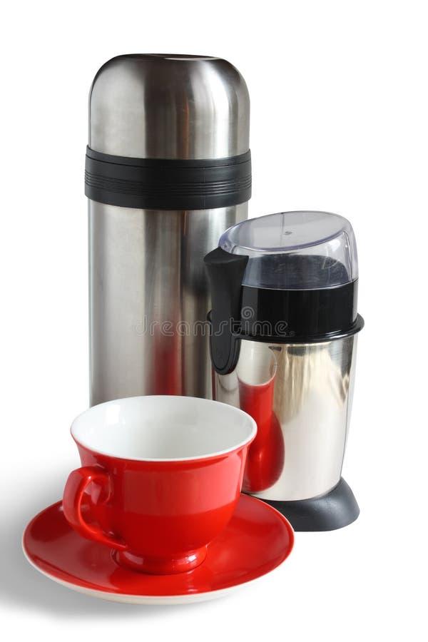 Amoladora de café eléctrica con el thermos y el casquillo rojo fotos de archivo