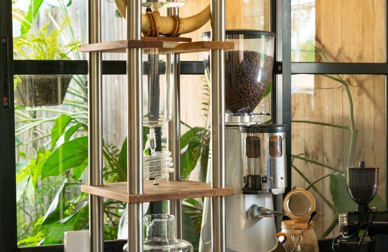 Amoladora de café en la tabla en cafetería imagenes de archivo