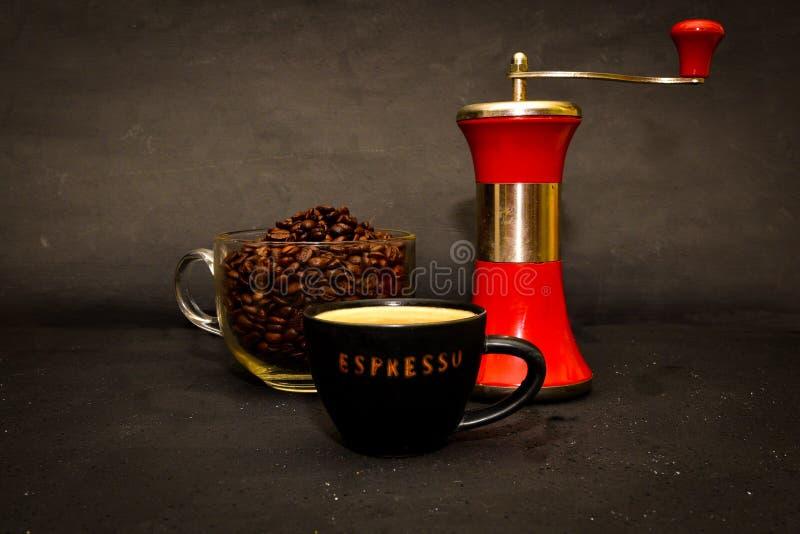 Amoladora de café roja del metal con una taza de café del café express fotos de archivo