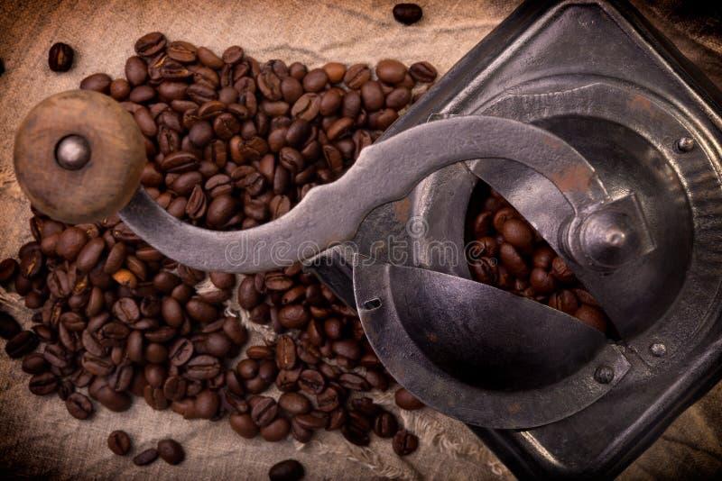 Amoladora de café vieja del metal por completo de los granos de café imágenes de archivo libres de regalías