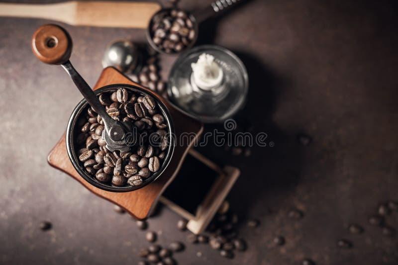 Amoladora de café y grano de café hermosos en la tabla de cocina vieja fotografía de archivo