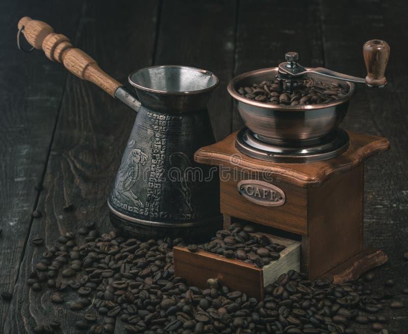 Amoladora de café y jezva con los granos de café en fondo oscuro imágenes de archivo libres de regalías