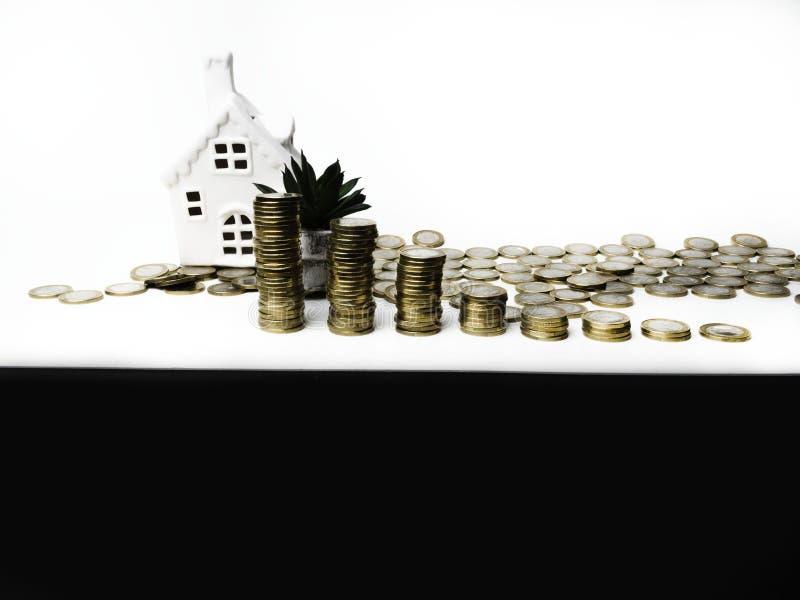 Amontonamiento de la torre y casa de las monedas de oro, dinero de ahorro y préstamo para las propiedades inmobiliarias de la con foto de archivo libre de regalías