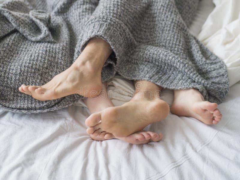Amor apaixonado Pés de um par novo que encontrando-se na cama na lua de mel Acople no amor que dorme sob a cobertura foto de stock