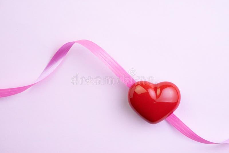 Amor, boda o fondo de día de San Valentín con forma roja del corazón y cintas rosadas en el papel rosa claro imágenes de archivo libres de regalías