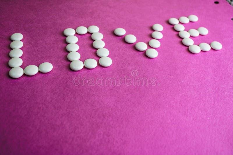 Amor bonito da inscrição feito dos comprimidos do círculo branco, das vitaminas, dos antibióticos e do espaço médicos lisos da có imagens de stock royalty free