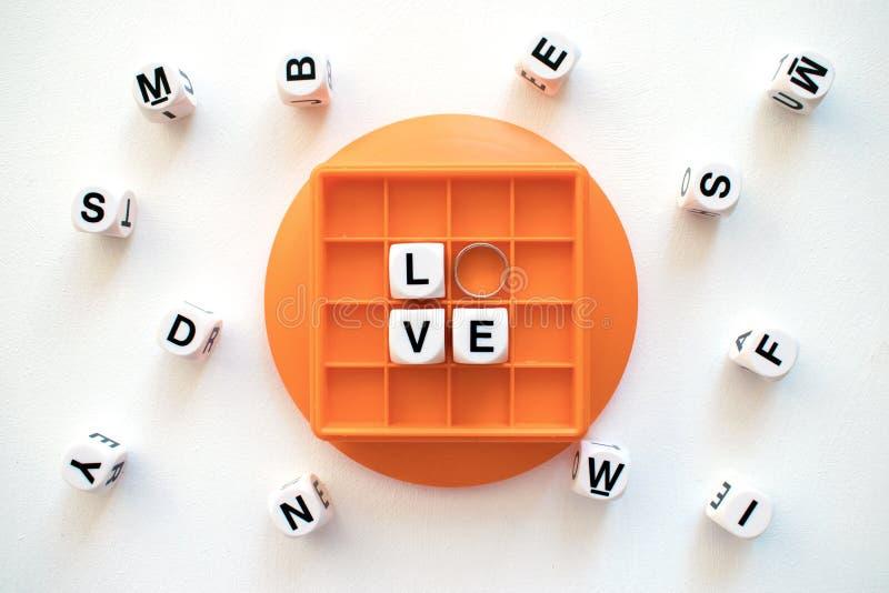 Amor branco da palavra do bloco com aliança de casamento de prata na caixa alaranjada fotografia de stock