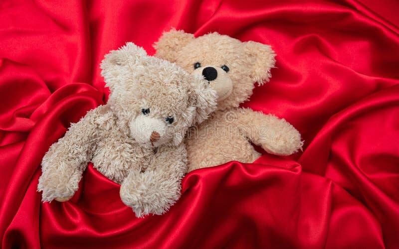 Amor, concepto, abrazo apretado Dos osos de peluche que abrazan como par en la cama, fondo rojo del satén imagen de archivo libre de regalías