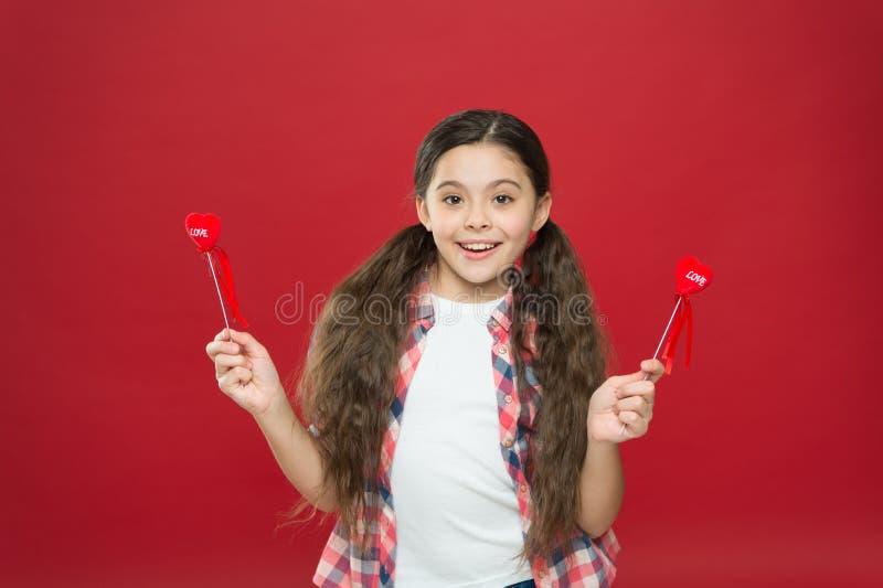 Amor da família Criança bonito da menina com corações Menina da criança com fundo vermelho do cabelo longo Comemore o dia de Vale fotos de stock royalty free