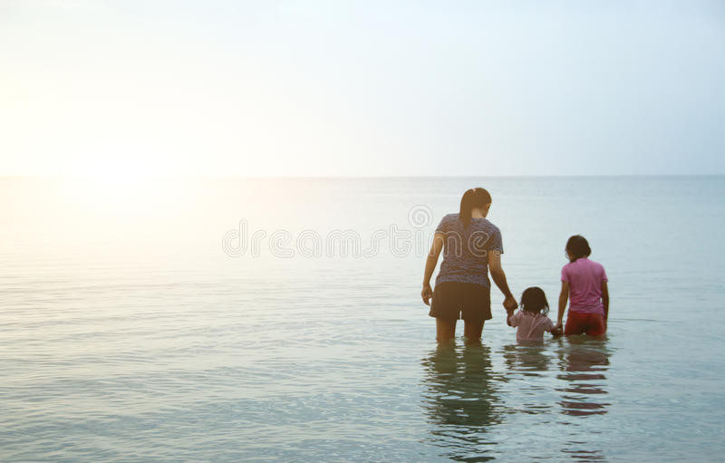 Amor da família que anda no oceano fotos de stock