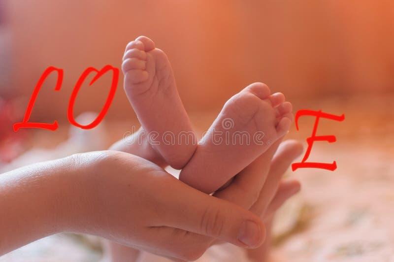 Amor da palavra com pés do bebê imagem de stock