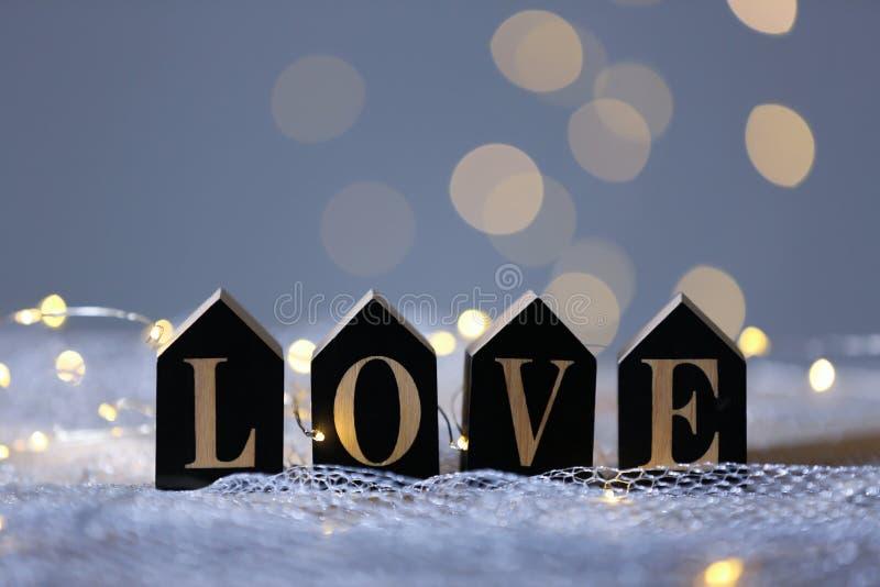 AMOR da palavra de letras de madeira na tela de malha contra luzes borradas Bokeh fotografia de stock