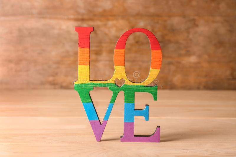 AMOR da palavra feito de letras do arco-íris na tabela de madeira Conceito de LGBT fotografia de stock