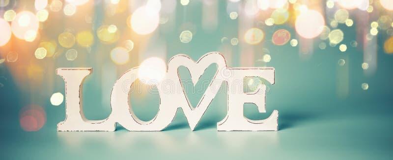 Amor de la palabra con la luz de oro del bokeh en fondo azul Partido de día de San Valentín o concepto abstracto del amor foto de archivo libre de regalías