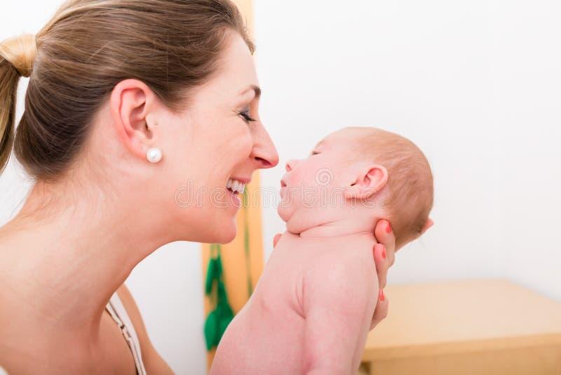 Amor de mãe de sorriso seu bebê recém-nascido imagens de stock royalty free