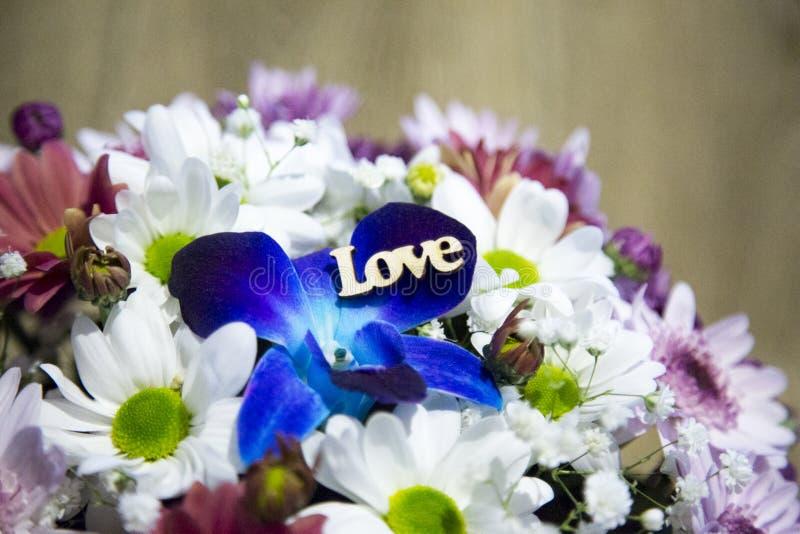 Amor de madeira da inscrição em uma pétala de uma flor azul Flores frescas na perspectiva de Ramalhete de flores da mola fotografia de stock royalty free