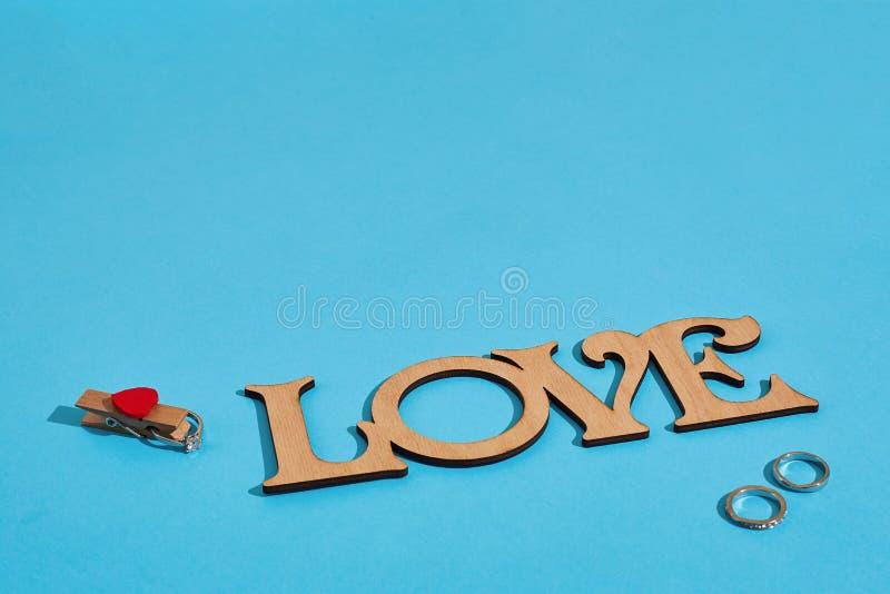 Amor de madera de la inscripción y el anillo en fondo azul Oferta de unión El concepto de día del ` s de la tarjeta del día de Sa fotografía de archivo libre de regalías