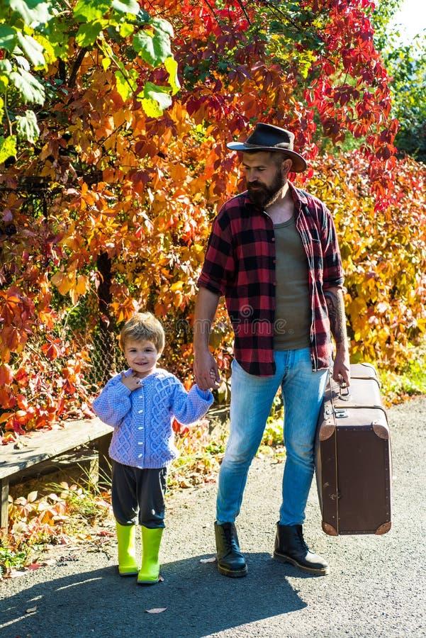 Amor de pais para o filho Estilo retro - pai com uma mala de viagem e seu filho Paizinho com o filho novo no parque do outono cur imagens de stock