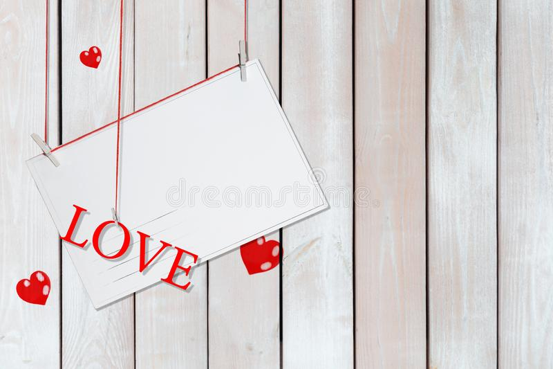 Amor de papel de la postal y de la palabra que cuelga en los hilos rojos rodeados de memoria con el espacio de la copia en el fon imagenes de archivo