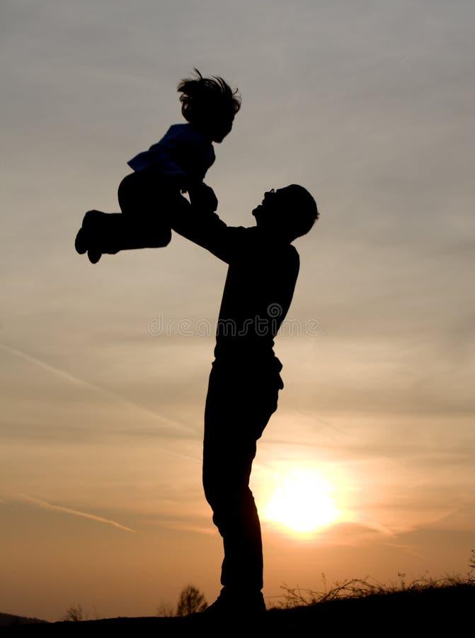 Amor do pai e da criança no por do sol imagem de stock royalty free