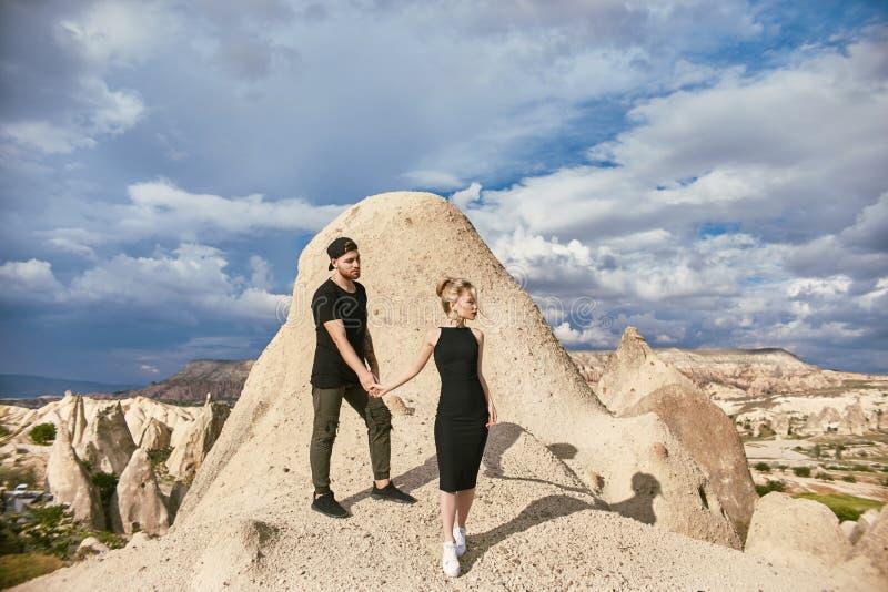 Amor e emoções que amam os pares que descansam em Turquia No amor o par oriental nas montanhas de Cappadocia abraça e beijos Clos fotos de stock royalty free