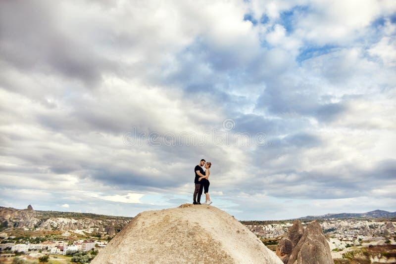 Amor e emoções que amam os pares que descansam em Turquia No amor o par oriental nas montanhas de Cappadocia abraça e beijos Clos imagem de stock