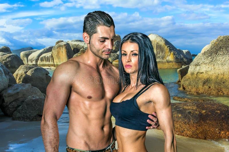 Amor e músculos na praia dos pedregulhos fotografia de stock