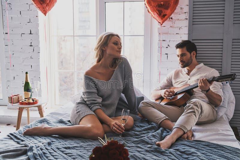 Amor em sua música Homem novo considerável que joga a guitarra a seu Beau foto de stock