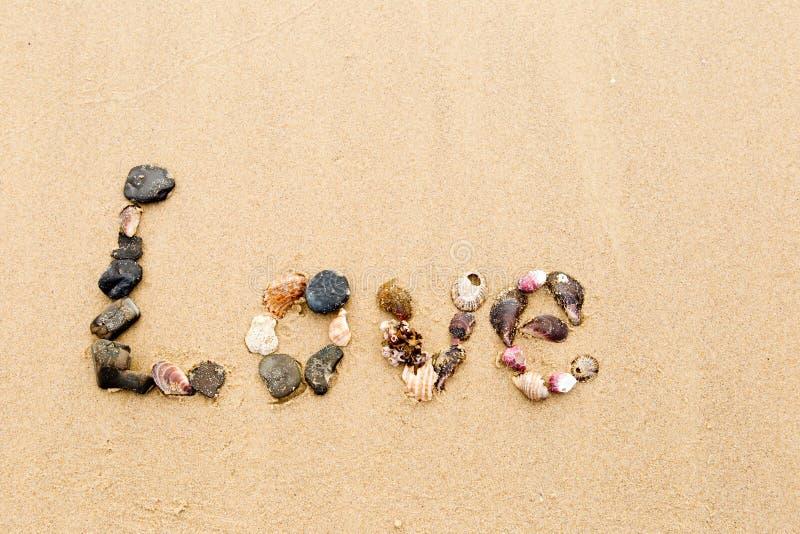 Amor escrito en conchas marinas en arena imagen de archivo libre de regalías