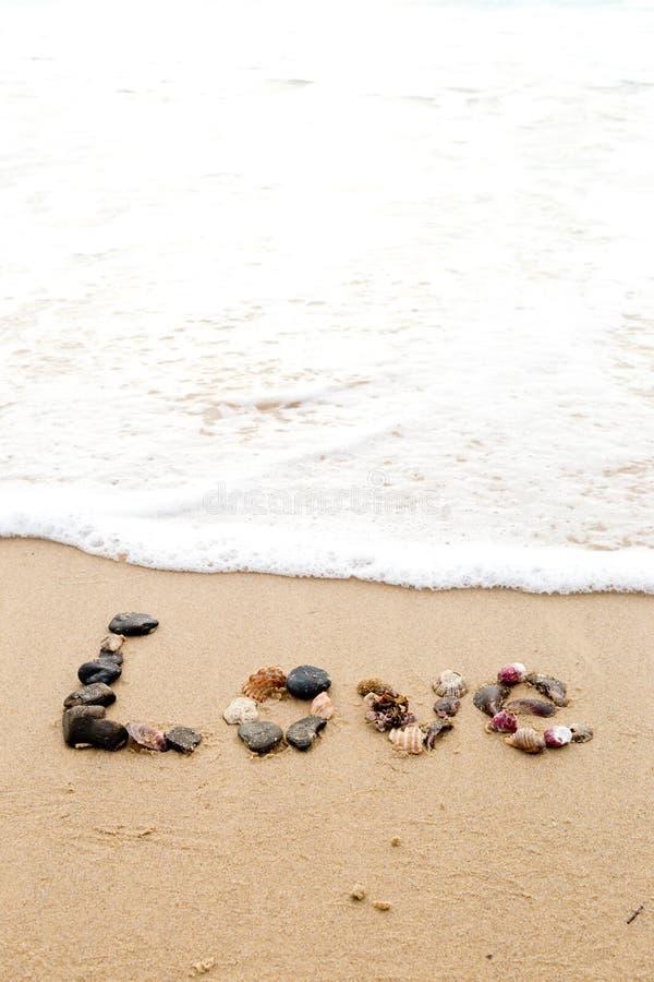 Amor escrito en conchas marinas en arena imagenes de archivo