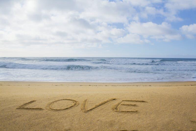 Amor escrito en la arena imagen de archivo