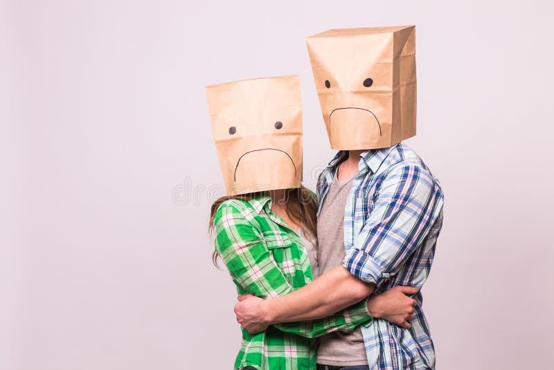Amor, família e conceito dos problemas do relacionamento - par infeliz que cobre suas caras tristes com o saco de papel sobre o b imagens de stock