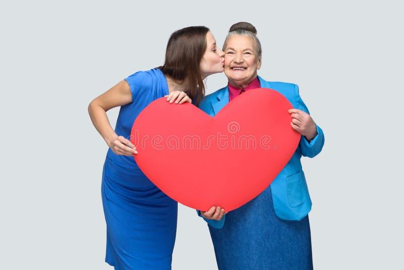 Amor grande na família Avó do beijo da jovem mulher fotos de stock royalty free