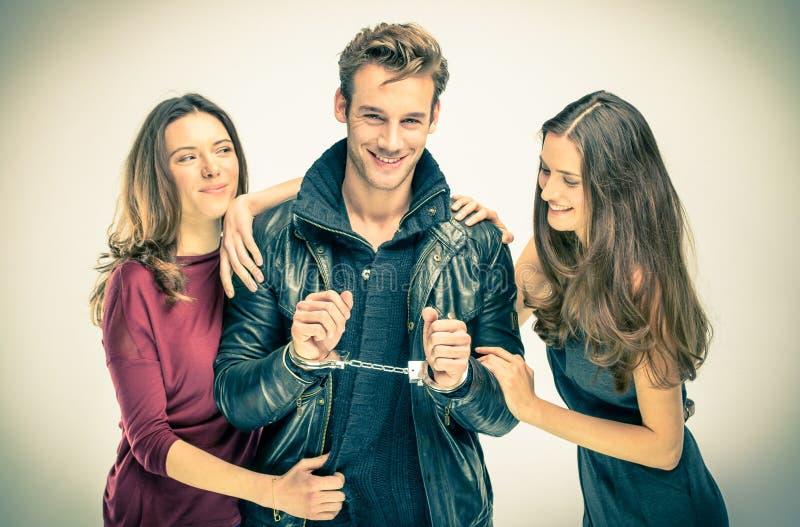 Amor moderno do threesome - duas mulheres com homem algemado fotografia de stock