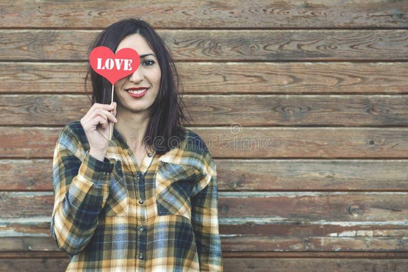 Amor, mujer joven con un corazón que cubre su ojo foto de archivo