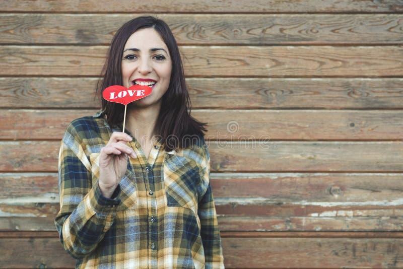 Amor, mujer joven que sostiene una piruleta en su boca imagen de archivo