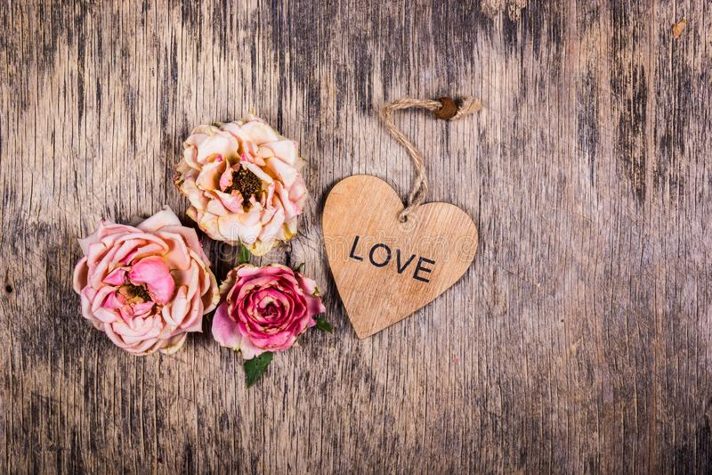 Amor murcho Amor passado metaphors Rosas inoperantes e um coração de madeira Conceito romântico fotografia de stock