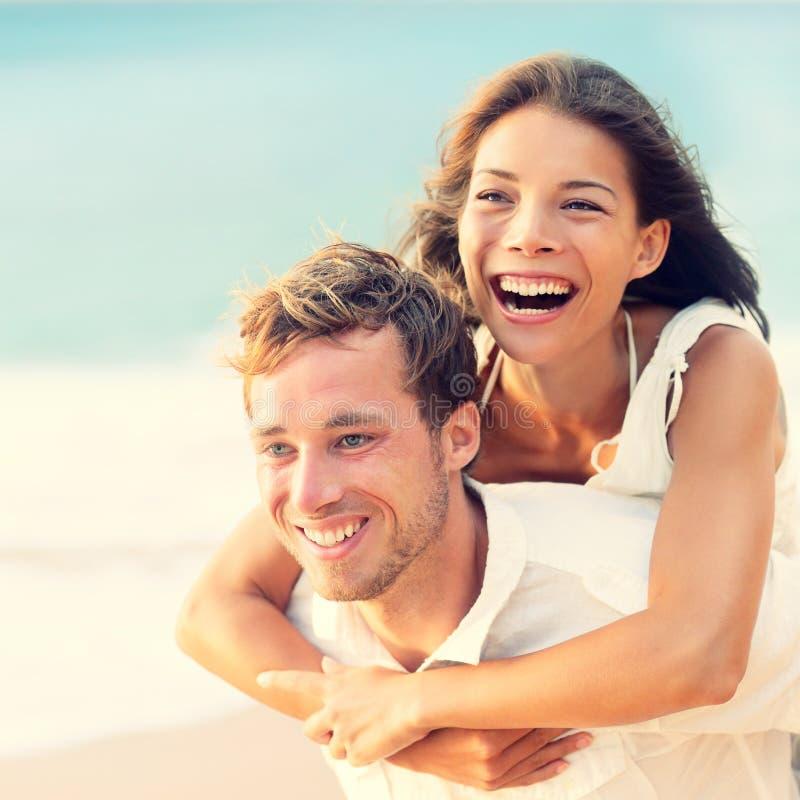 Amor - par feliz en la playa que tiene transporte por ferrocarril de la diversión foto de archivo libre de regalías