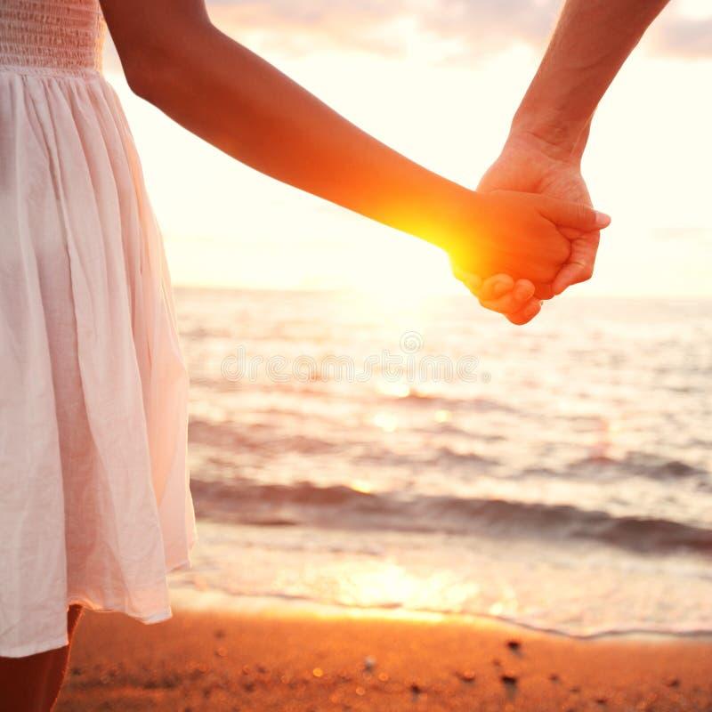 Amor - par romântico que guardara as mãos, por do sol da praia imagem de stock