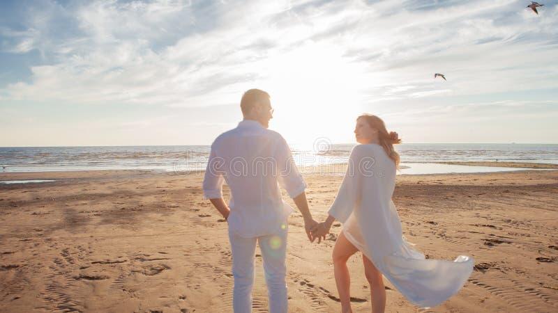 Amor, romance en la playa Pares hermosos jovenes, mujer, hombre, en la ropa que vuela floja blanca, paseo, a lo largo de la costa imagenes de archivo