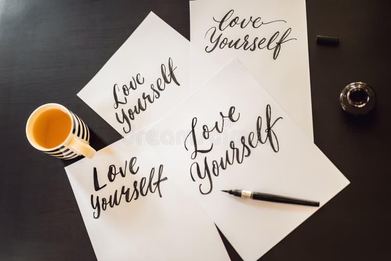 Amor usted mismo El cal?grafo Young Woman escribe frase en el Libro Blanco Inscripci?n de letras adornadas ornamentales imágenes de archivo libres de regalías
