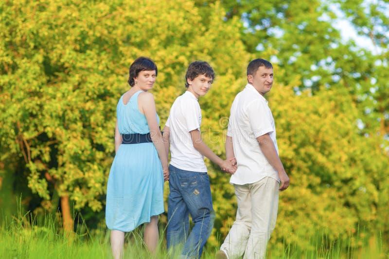 Amor y conceptos e ideas de la dulzura Familia caucásica del tiempo de gasto tres junto abrazado en parque del verano imagen de archivo