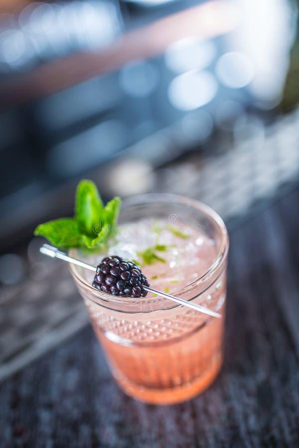 Amora da bebida do cocktail com bagas e a hortelã pretas no barcounter no clube noturno ou no restaurante imagens de stock