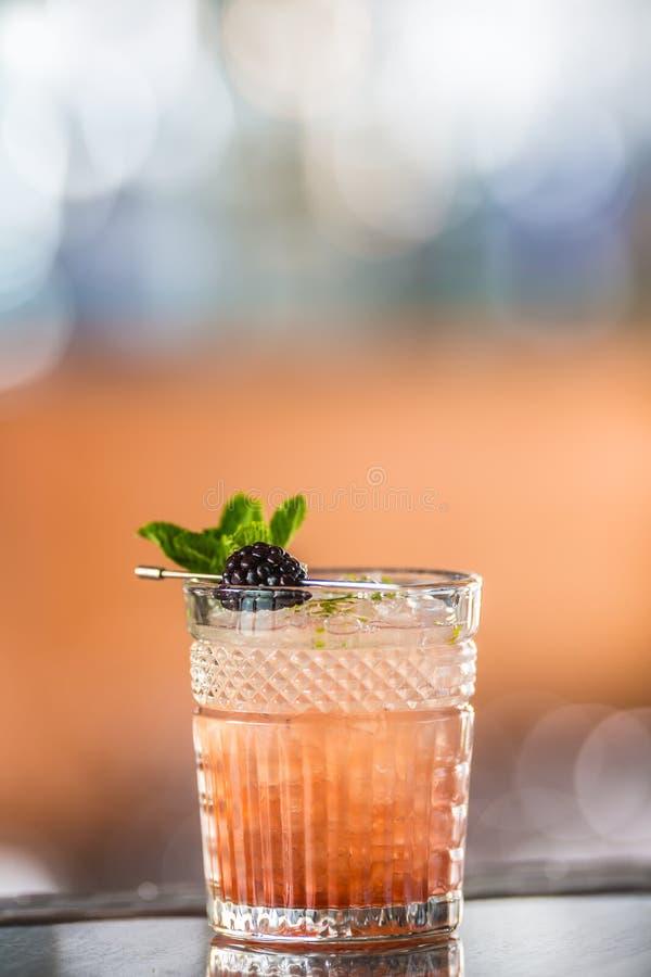 Amora da bebida do cocktail com bagas e a hortelã pretas no barcounter no clube noturno ou no restaurante imagem de stock royalty free